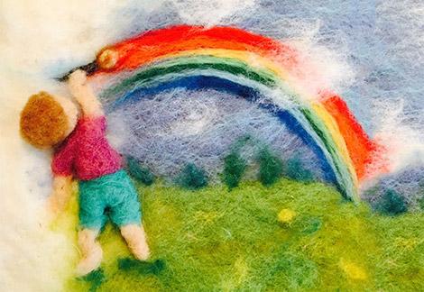 עבודת ליבוד. ילד מצייר קשת בענן